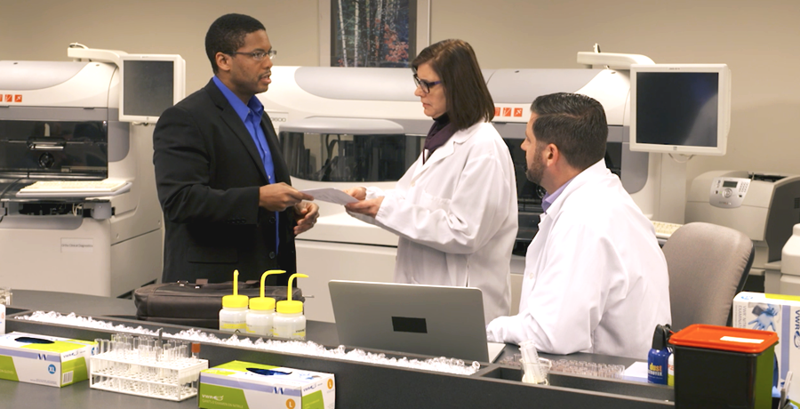 Image of an Ortho Account Manager in the lab with two customers